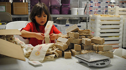 Child bagging soap for family's e-commerce business