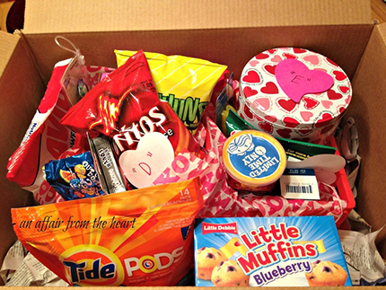 An opened care package box with snack food items inside
