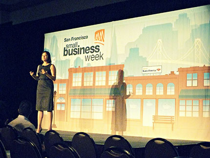 Ecommerce business owner, Lenora Estrada, stands up on stage at San Francisco Small Business Week.